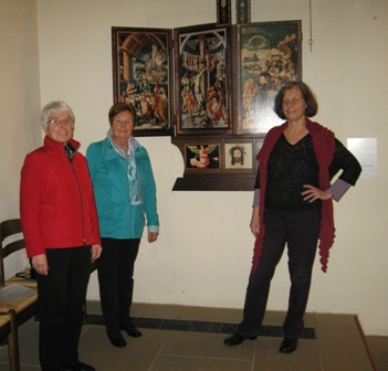 Foto von drei Akteurinnen der Frauengeschichtswerkstatt vor dem Ratgeb-Altar in der Herrenberger Stiftskirche.